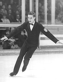 A young male figure skater is performing in an ice rink with a crowd in the background stands. He wears a formal black suit with white shirt and black bow tie, and his short hair is well combed.