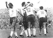 Football players in white shirts and dark shorts celebrate together