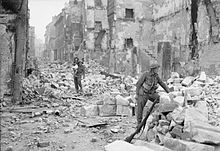 Two soldiers in a rubble-filled street bordered by badly-damaged buildings; one is clambering over the debris with a young child on his shoulder