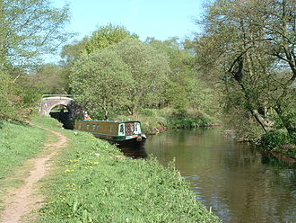 Caldon Canal - A narrowboat has just locked down into the Churnet river at Oak Meadow Ford lock