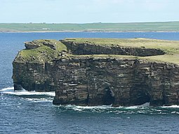 Grey Head, the northern tip of the Calf. Sea caves, and the beginning of an arch can be seen in the cliff.