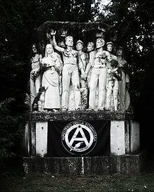 """El monumento con el título """"Cararia"""", el nombre latino de Carrara , representa a Alberto Meschi en el centro de la escultura, en defensa fraterna y firme de un grupo de canteros, acompañados por niños y una mujer que rodea al líder sindical. A los lados de la inscripción, las mejoras en el tiempo de trabajo obtenidas por la Cámara de Trabajo de Carrara bajo la guía de A. Meschi: canteros 6/5 horas; mineros a las 6."""