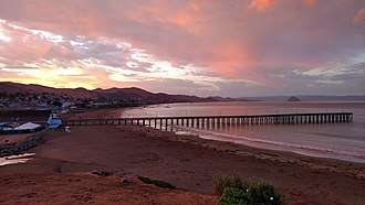 Cayucos, California - Cayucos Pier and Cayucos State Beach at sunrise with Morro Rock visible in the background