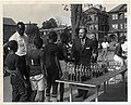 Children line up to receive basketball trophies from Boston Police Commissioner Edmund McNamara. Satch Sanders of the Boston Celtics watches on from the left (12461956653).jpg