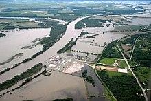 Widok z lotu ptaka na gospodarstwa i elektrownię na obszarach wiejskich częściowo zalanych przez rzekę, która przelewała się przez jej brzegi