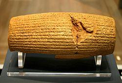 Tampak depan silinder tanah liat yang diletakkan pada landasan. Silinder ini dipenuhi permukaannya dengan baris-baris tulisan kuneiform
