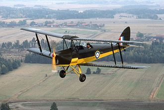 British Commonwealth Air Training Plan - The ubiquitous DH 82 Tiger Moth, shown here in camouflaged upper surfaces, yellow lower surfaces, denoting a UK-based aircraft, was in use by all Commonwealth training units. In other BCATP areas the camouflage was dispensed with.