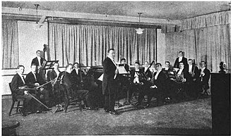 WWJ (AM) - 1922 Detroit News Orchestra broadcast. The large round unit atop the stand on the far right foreground is the pick-up microphone.