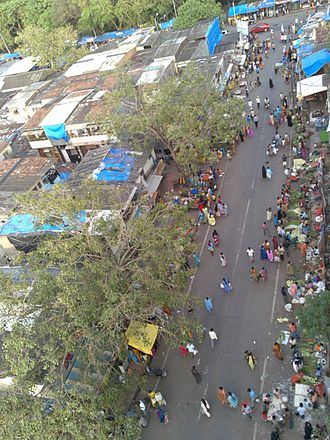 Dharavi - Street vendors and farmers market along the road passing through Dharavi slum in Mumbai.