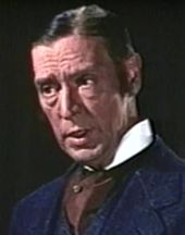 Color screenshot a white man with dark hair wearing a blue suite with a maroon cravat and a white collar.