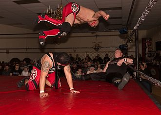 The Latin American Xchange - EYFBO (Angel Ortiz kneeling and Mike Draztik in midair) executing an assisted cannonball on Rickey Shane Page