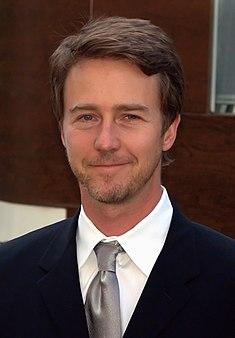 A portrait of Edward Norton, a blonde Caucasian man in a white plaid shirt. He is smiling towards the camera