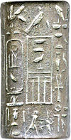Small cylinder of grey silver with hieroglyphic signs inscribed on it