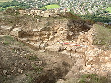 A low stone wall being excavated, with a town in the background.