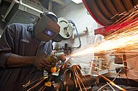 Flickr - Official U.S. Navy Imagery - A Sailor grinds a metal fitting in the general workshop..jpg