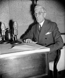 Francis Townsend, seated at desk, with microphones, c. 1939