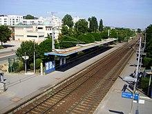 Vue aérienne de la gare de Chanteloup-les-Vignes, surplombée par des barres de HLM