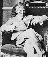 A middle-aged man sitting with his legs crossed in an armchair, looking over the top of his glasses while holding a book