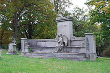 Short, wide memorial lined by a bench with angel statue sitting on the bench. Material is grey and central pillar depicts the name Giles.