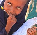 Girl studying waiting for food aid, Somali region of Ethiopia (25856182548).jpg