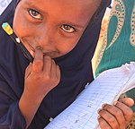 Girl studying waiting for food aid, Somali region of Ethiopia (25856182548).jpg