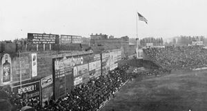 "Green Monster - The original ad-covered Green Monster in 1914, with fan seating in front of the wall's base, atop ""Duffy's Cliff"" (seen in the distance, nearest the flagpole)."