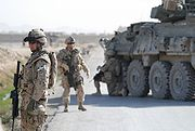 Canadian Grenadier Guards in Kandahar Province standing by road with armored car