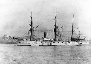 Broadside view of a metal ship, quiet at anchor in a port. Two small boats are alongside. There are three masts but no sails are set. There is a large smokestack amidships. Guns are sponsoned out from the sides, with gunports between them.