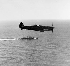 HMS Royalist (89) - A Supermarine Seafire of 807 Naval Air Squadron Fleet Air Arm flying above HMS Royalist during a training flight from the Royal Naval Air Station at Dekhelia, near Alexandria, in Egypt, in February 1945.