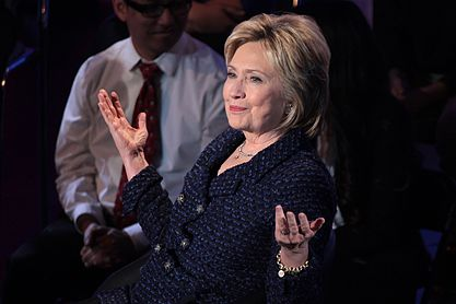 Clinton speaking behind a podium with a microphone in her hand. She is speaking at the Brown and Black Presidential Forum in Des Moines, Iowa, on January 11, 2016.