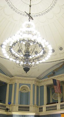 A room with high ornate blue-and-white walls and a white-domed ceiling, from which a large chandelier hangs by a rod. Along the rod, between the chandalier and the ceiling, is the figure of a fish.