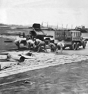 Advanced Landing Ground - IX Engineering Command putting down a Pierced Steel Planking (PSP) Runway at an Advanced Landing Ground under construction