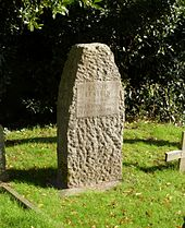 A narrow granite headstone with rough surface finish in a grassy cemetery