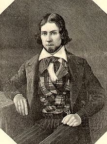 Engraving of a young man with hair parted in the middle, wearing a plaid vest  and suit coat. He is looking at the viewer.