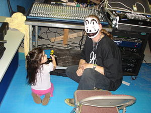 Juggalo - A man in Juggalo face paint kneels next to a small child.