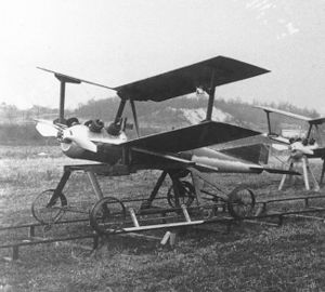 a small unmanned biplane aircraft resting on a pair of rails