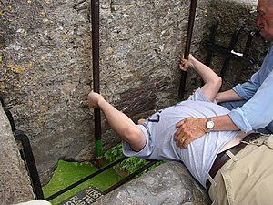 Person kissing the Blarney Stone at Blarney Ca...