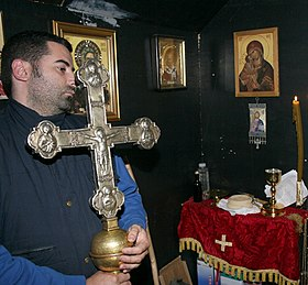 Photograph of a man in his thirties holding a large silvery cross in a room on whose walls religious paintings are hung.