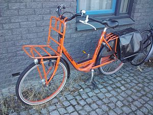 Luggage carrier - A porteur-style front rack and rear rack with panniers on a utility bicycle.