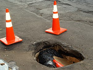 Pothole - A deep pothole with a nearby patched area on New York City's Second Avenue