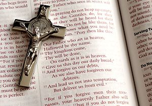 Lord's Prayer - A crucifix on an open Bible showing an English translation of the prayer (from Matthew)