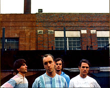 The band members in front of an industrial building