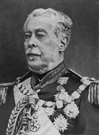 Half-length photographic portrait of an older man dressed in a military tunic with medals, chain of office and sash