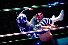 A masked wrestler executing a flying headscissorts, wrapping his legs around the head of his opponent, trying to throw him to the ground.