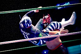 A color photograph of a wrestler in black and white gear, including a black and white mask executing a head scissors takedown on a wrestler in black and red mask with ornamental horns.