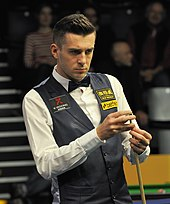 Mark Selby stands looking at a table while he chalks the cue in his left hand.