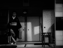 A middle-aged Japanese woman, wearing a kimono and carrying a suitcase in her left hand and a valise in her right, in the process of walking around the perimeter of a small room. There is a bookcase on the left and a straight-backed chair on the right and screens and a ceiling lamp in the near background.