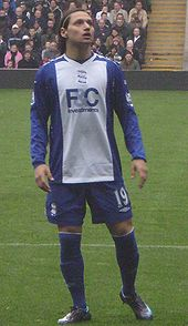 Dark-haired young man wearing blue and white football kit.