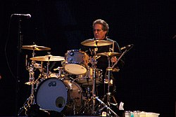 Middle-aged man with slightly graying dark hair and glasses wearing black shirt sits behind a silver-colored, gold-lit drum kit with his left hand and stick about to hit a cymbal and his eyes fixed straight ahead.