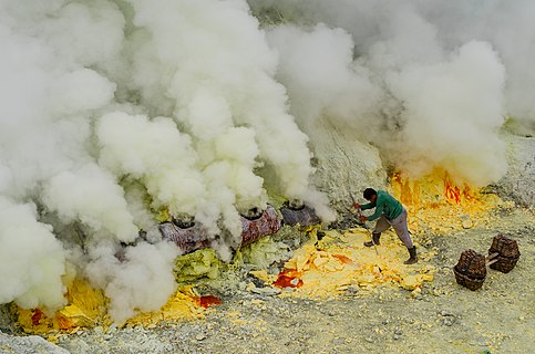 Sulfur miners collecting frozen sulfur from the crater of Mount Ijen